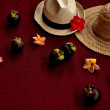 Foto Stock: Straw hats with mangosteen on exotic dark red background
