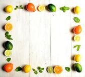 Colorful citrus fruits with mint leaves on white wood background — Stock Photo