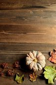 Pumpkin with fall leaves on wood background — Stock Photo