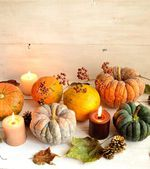 Pumpkins with candles on white wood background — Stock Photo