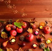 Autumn fruits with fall leaves on brown wood background — Stockfoto