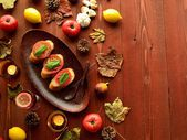 Bruschetta with fall leaf on brown wood background — Stock Photo
