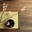 Cherry blossoms on Japanese tatami mat — Stock Photo #40216173