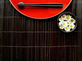 Chopsticks,flowers and Japanese red tray — Stock Photo