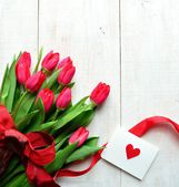Red tulips bouquet with message card — Stock Photo