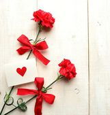 Red carnations with message card — Stock fotografie