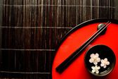 Japanese red tray,chopsticks and cherry blossoms — Stock Photo