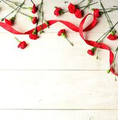 Red carnations with red ribbon — Stock Photo