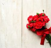 Red carnations bouquet on white wooden background — Stockfoto