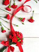 Rote nelken strauß mit schleife — Stockfoto