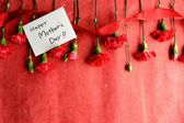"""""""mors dag"""" meddelande kort med nejlikor på röd bakgrund — Stockfoto"""