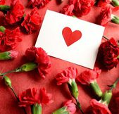 Heart message card on red carnations background — Stockfoto