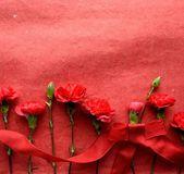 Rött band och röda nejlikor på röd bakgrund — Stockfoto