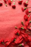 Red ribbon and red carnations on red background — Stock Photo