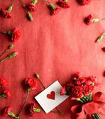 Red carnations bouquet with heart message card — Stock Photo