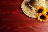 Straw hat with sun flowers — Stock Photo
