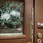 Broken window on door by vandalism — Stock Photo