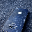 Black iPhone  with broken display laying on asphalt — Stock Photo