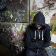 A young against a wall with graffiti — Stock Photo