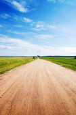 Long road to green fields. — Stock Photo