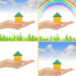 Color house in hand rainbow blue summer sky green grass - Stock Photo