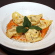 Tortelloni with sauce and parmesan on white plate — Stock Photo
