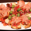 Plate of bruschetti with ham and green olives — Stockfoto