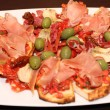 Plate of bruschetti with ham and green olives — 图库照片
