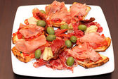 Closeup of the bruschetti with ham and olives on a plate at restaurant — Stock Photo
