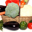Fresh organic vegetables in wicker basket over white background — Stockfoto