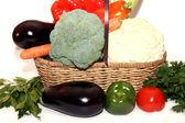 Fresh organic vegetables in wicker basket over white background — Stock Photo