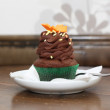 Ornated cupcake on white plate — Zdjęcie stockowe