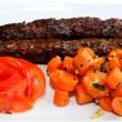 Stock Photo: Closeup scene of grilled meat with carrots saute and salad