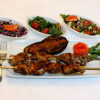 Grilled meat with eggplant and salad on restaurant table — Stock Photo