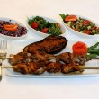 Stock Photo: Grilled meat with eggplant and salad on restaurant table