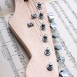 Electric guitar fretboard and music sheet — Stock Photo #42053423