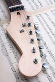 Electric guitar fretboard and music sheet — Stock Photo