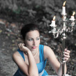 Girl sits near table with red roses and keeps candlestick with t — Stock Photo #49711593