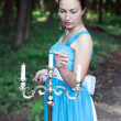 Girl sets fire three candles on a silver candlestick in a forest — Stock Photo #49931899