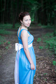 Girl walking on the dark green forest turns around — Stock Photo