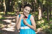 The smiling girl in a forest with red rose in her hand  — Stock Photo