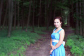 Smiling girl stands on a footpath of dark forest — Stock Photo