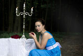 Girl keeps rose and sits near a table with a silver candlestick  — Stockfoto