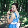 Girl turns around with red rose in her hand in the dark forest — Stock Photo #51236127