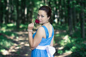 Girl turns around with red rose in her hand in the dark forest — Stockfoto