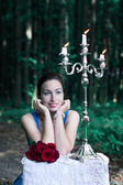 Smiling girl sits at a table with a bouquet of red roses and sil — Stock Photo