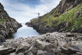 Rocky coastline and lighthouse, Northen Ireland — Stock Photo
