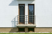 Wooden tall windows in white wall — Stock Photo