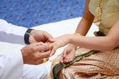 Groom wears a diamond ring onto the brides hand — Stock Photo