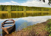 Beautiful summer landscape on the river with a boat — Stock Photo
